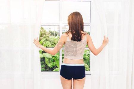 Foto de Mujer despertar y abrir las cortinas de la ventana y ella se siente feliz y relajado, respirar aire fresco por la mañana - Imagen libre de derechos