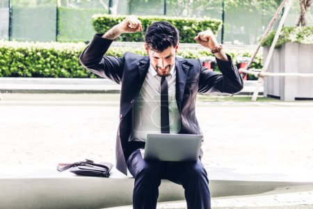 Photo pour Succès d'un bel homme d'affaires en costume élégant noir assis célébrant avec les bras levés et travaillant avec un ordinateur portable sur la ville.Entreprise et démarrage - image libre de droit