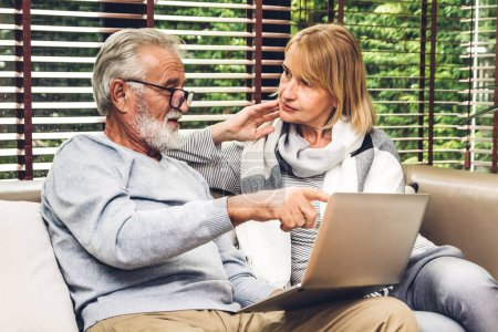 Photo for Senior couple relaxing and using laptop computer together sitting on sofa in living room at home.Retirement couple concept - Royalty Free Image