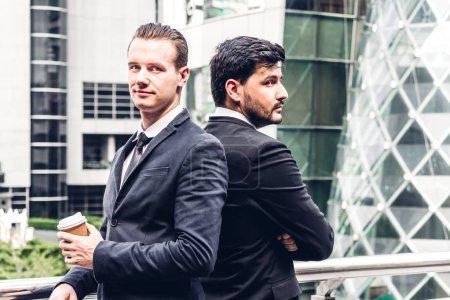 Photo pour Deux collaborateurs d'homme d'affaires souriant en noir costume debout avec les bras croisés dans la ville moderne. travail d'équipe et le concept de partenariat - image libre de droit