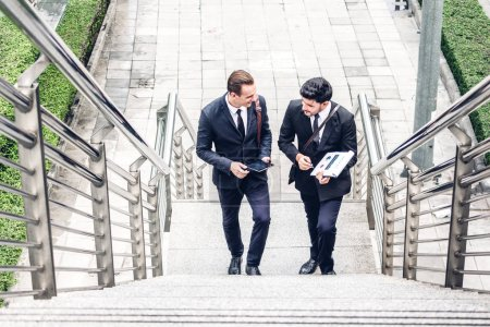 Photo for Two smiling businessman coworkers in black suit talking and walking.business people discussing strategy in the modern city.teamwork and Partnership concept - Royalty Free Image