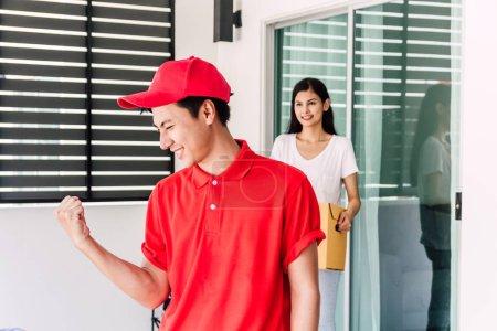 Photo pour Femme acceptant une livraison des boîtes de livreur dans le concept de service uniform.courier rouge - image libre de droit