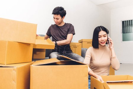 Photo for Happy young couple unpacking box and moving into their new home.House moving and real estate concept - Royalty Free Image