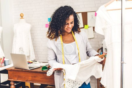 Photo for Smiling african american black woman fashion designer standing  working and holding dress at workshop studio - Royalty Free Image