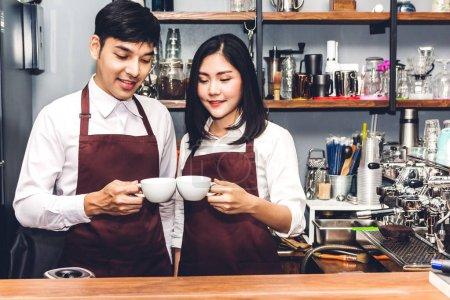 Photo pour Portrait de la propriétaire de petite entreprise du couple souriant et travaillant derrière le bar comptoir dans un café. Barista de couple à l'aide de machine à café pour préparer du café au café - image libre de droit
