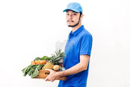 Photo pour Heureux livreur en uniforme bleu, transportant le paquet d'aliments d'épicerie avec des légumes et de fruits sur fond blanc - image libre de droit