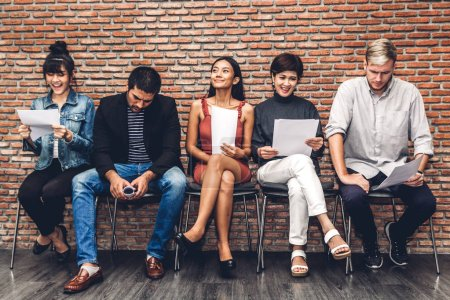 Photo for Group of business people holding paper while sitting on chair waiting for job interview against brick background - Royalty Free Image