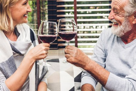 Photo for Senior couple relax talking and drinking wine glasses together on sofa in living room at home.Retirement couple concept - Royalty Free Image