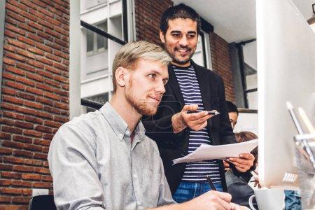 Foto de Grupo de negocios informal trabajando y discutiendo la estrategia con escritorio computer.creative negocios planificación y lluvia de ideas en workloft moderna. Concepto de trabajo en equipo - Imagen libre de derechos