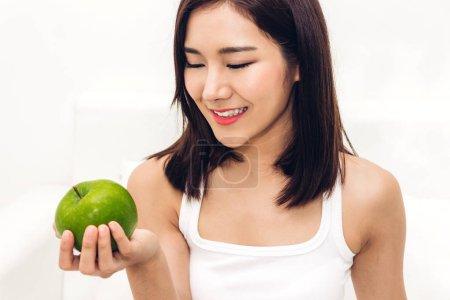 Photo pour Femme tenant et manger une pomme verte fraîche sur blanc background.dieting concept.healthy lifestyle - image libre de droit