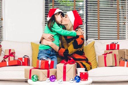 Photo pour Mère et fille en chapeaux santa s'amuser et échanger des boîte de dons près de décoration de Noël à la maison. Joyeux Noël et bonne année new concept - image libre de droit
