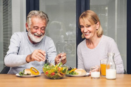Senior couple enjoy eating  healthy breakfast together in the kitchen.Retirement couple concept