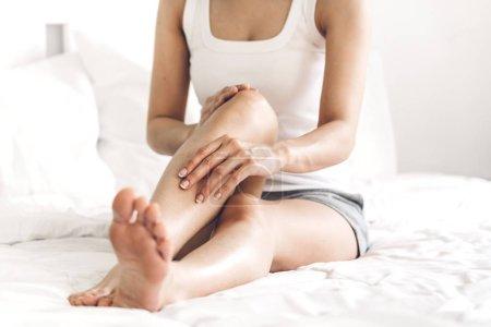 Beautiful woman beauty health care.beauty and spa.perfect fresh skin.Woman applying moisturizing cream on long legs at home