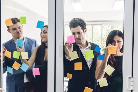 Photo for Group of casual business people planning and brainstorm writing over the project with stickers note on glass window at modern office.Teamwork concept - Royalty Free Image