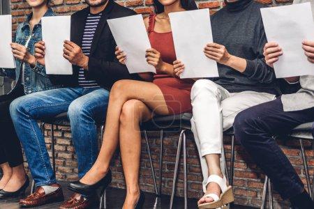 Foto de Grupo de empresarios sosteniendo papel mientras están sentados en la silla esperando una entrevista de trabajo contra el fondo de la pared - Imagen libre de derechos