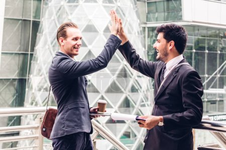 Photo for Successful business team giving a high fives gesture at city background - Royalty Free Image