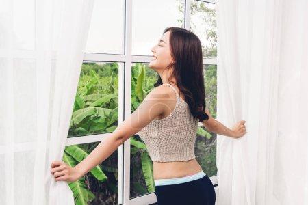 Photo pour Femme se réveillant et ouvrant rideaux de fenêtre et elle se sent heureuse et détendue respirant l'air frais le matin - image libre de droit