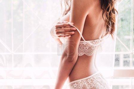 Photo pour Jeune femme sexy en slip décrocher et de décoller sur son soutien-gorge blanc dans la salle - image libre de droit