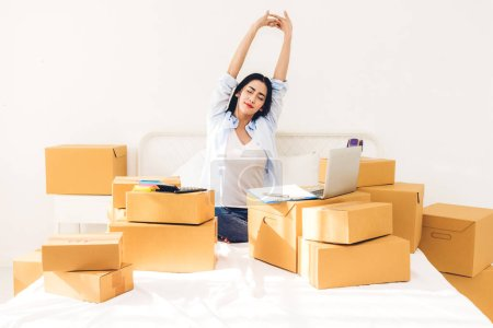Photo for Young woman freelancer working and use laptop computer with cardboard box on bed at home - SME business online and delivery concept - Royalty Free Image
