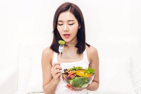 Photo pour Femme heureuse manger et montrant sain salade fraîche dans un style de vie concept.healthy bowl.dieting avec de la nourriture verte - image libre de droit
