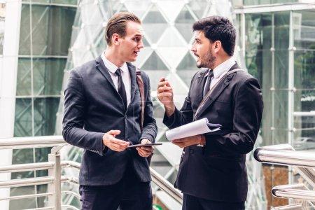 Photo pour Deux collaborateurs d'homme d'affaires souriant en noir costume parler et walking.business les gens discuter de stratégie dans la cité moderne - image libre de droit