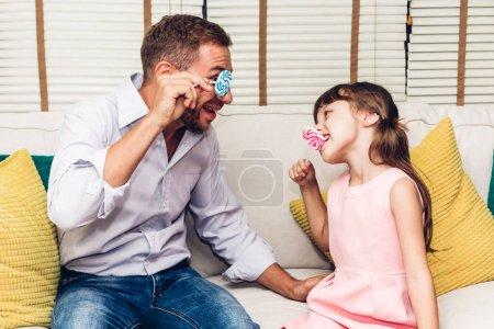 Photo for Father with little daughter having fun and playing together on the sofa at home.Love of family and father day concept - Royalty Free Image