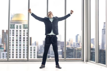 Photo for Successful of businessman in black elegant suit standing celebrating with arms up on modern city background.Business and success concept - Royalty Free Image