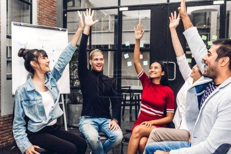 Photo pour Succès du groupe d'entreprises occasionnelles discutant et travaillant .creative gens d'affaires célébrant avec les bras levés dans le loft.Teamwork moderne concept - image libre de droit