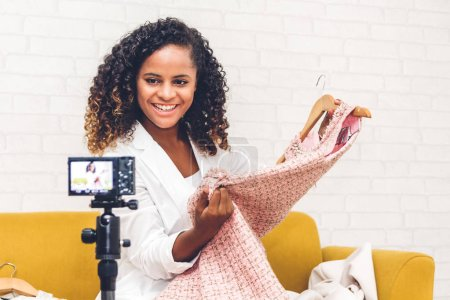 Photo for African american woman blogger in front of camera recording vlog herself talking about with clothes at home.fashion shopping and social media concept - Royalty Free Image