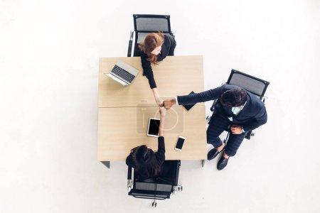 Photo for Top view of successful of group business people fist bump together on wooden desk at office.Friendship teamwork concept - Royalty Free Image