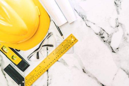 Photo pour Outils de construction avec casque de sécurité sur fond de marbre blanc - image libre de droit