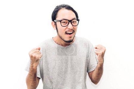 Photo pour Succès de happy souriant jeune asiatique beau homme triomphe célébrant les bras vers le haut sur fond blanc - image libre de droit