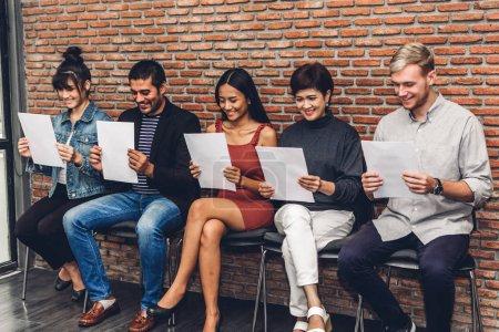 Photo pour Groupe de gens d'affaires tenant papier tout en étant assis sur la chaise d'attente pour l'entrevue d'emploi sur fond de mur - image libre de droit