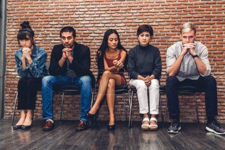 Photo pour Groupe de gens d'affaires assis sur la chaise en attendant un entretien d'embauche sur fond de mur - image libre de droit