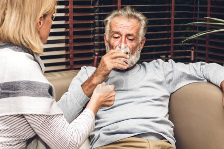 Photo for Senior man holding bottle with pills and taking medicine with glass of water sitting on sofa in living room at home. Healthcare senior people concept - Royalty Free Image