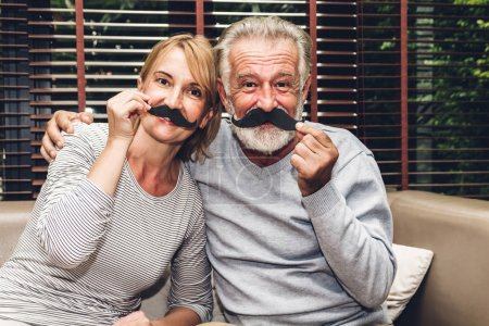 Photo for Happy smiling elder senior couple hugging relaxing and talking together sitting on sofa in living room at home.Retirement couple concept - Royalty Free Image