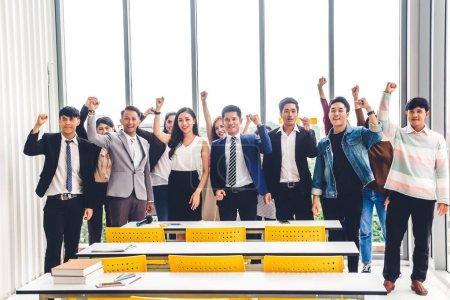 Photo pour Le succès du groupe de vêtements de travail relax célébrer leur triomphe avec les bras vers le haut en workloft moderne. Concept de travail d'équipe - image libre de droit