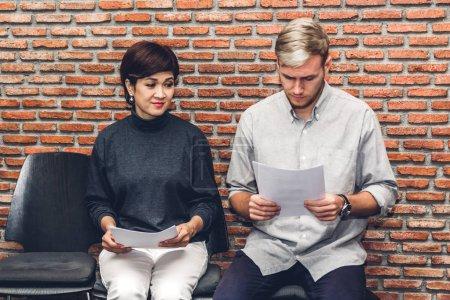 Photo pour Les gens d'affaires tenant du papier tout en étant assis sur la chaise en attendant l'entrevue d'emploi sur fond de mur - image libre de droit