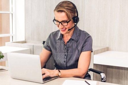 Photo pour Belle femme d'affaires services de soutien à la clientèle travaillant avec casque et ordinateur au centre d'appels - image libre de droit