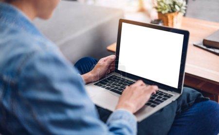 Photo pour Jeune femme créative se détendre en utilisant un ordinateur portable de travail et dactylographier sur le clavier avec des écrans blancs maquette blanche à la maison - image libre de droit