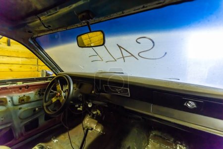 Photo pour Vue intérieure de l'intérieur de la vieille voiture cassée avec tableau de bord du véhicule poussiéreux, rétroviseur, volant et pare-brise sale avec titre VENTE écrit à l'extérieur. Concept de vente de voitures d'occasion sur le - image libre de droit