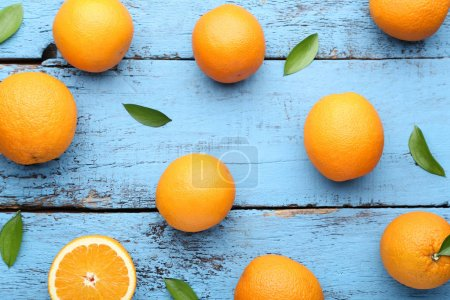 Photo for Oranges with green leaves on blue wooden table - Royalty Free Image
