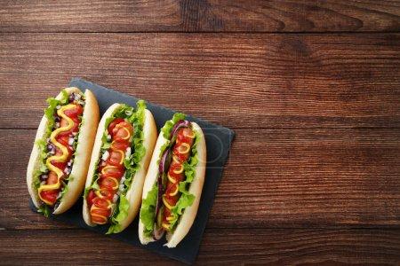 Photo pour Hot dogs au ketchup, moutarde et légumes sur table en bois - image libre de droit