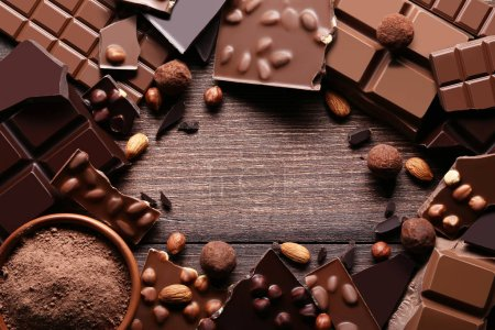 Chocolate pieces with nuts and cocoa powder in bowl on wooden table