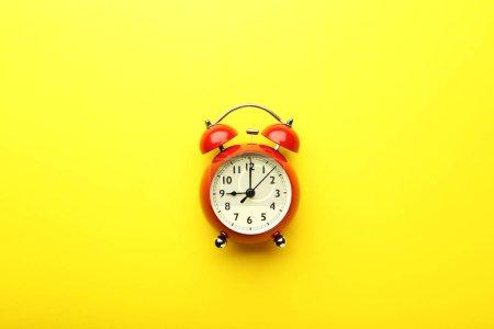 Photo pour Réveil rouge sur fond jaune - image libre de droit