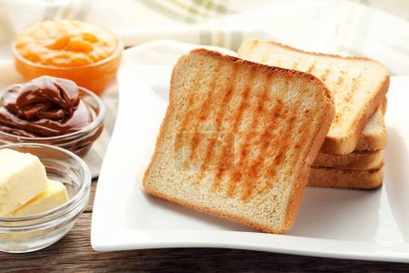 Photo for Toast bread in plate with bowls of butter and jam on wooden table - Royalty Free Image