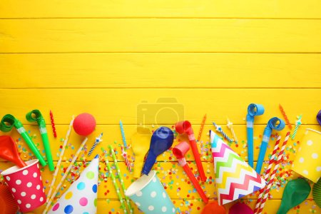 Birthday party caps, blowers and candles on wooden table
