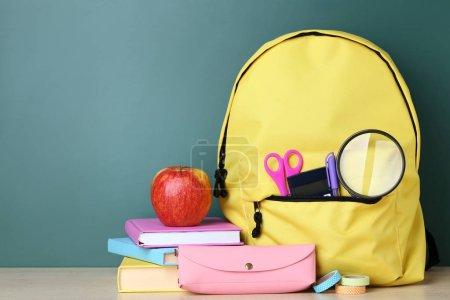 Photo pour Sac à dos jaune avec fournitures scolaires sur fond vert - image libre de droit