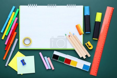School supplies with blank sheet of paper on chalkboard background