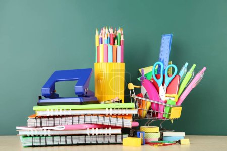 School supplies with notebooks on chalkboard background